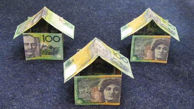 3 houses made of $100 notes