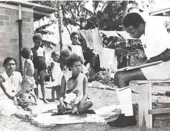 A census collector in Papua New Guinea 1966, collects information from a family