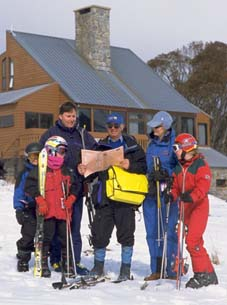 1986 photograph of a census collector with a family in ski gear at a snowfield.