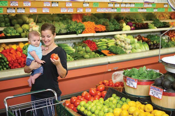 Mother and child in fruit and vegetable aisle of a supermarket