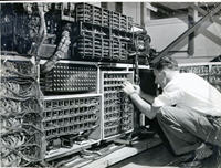 George Crossman undertaking maintenance at the back of a Census trio machine, showing large quantities of wiring