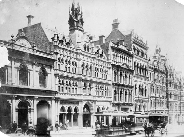 Photograph of the old Rialto Building, Collins street Melbourne. Trams and horse drawn carriages can be seen on the street.