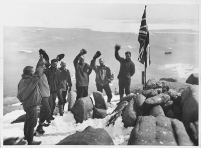 Cheering the flag... A scene on the heights overlooking Proclamation Harbour, Enderby Land, where the Union Jack was raised by Sir Douglas Mawson and his colleagues. At the foot of the flagstaff, official records were buried in a sealed receptacle.