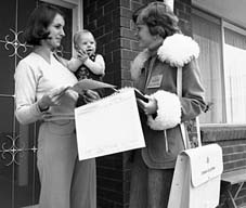 Photograph of a woman census collector on a doorstep talking to a woman holding a child