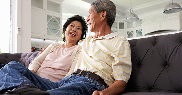 Older couple laughing in living room