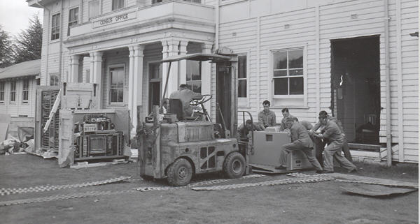 Six men in overalls assist a forklift driver in loading a Census Trio machine  so that he canl lift it through a large hole cut in the building