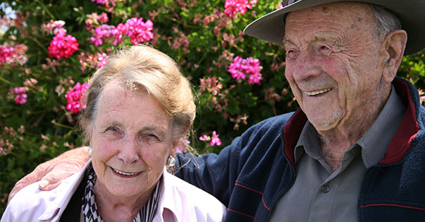 Older couple standing in garden